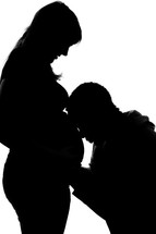 Silhouette of a man kneeling and praying for his wife and their unborn child.