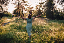 Woman enjoying nature with raising her arms