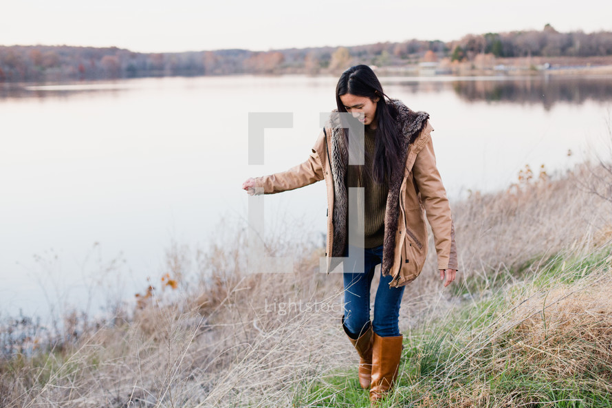 young woman walking outdoors in coat and boots