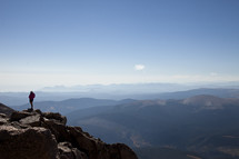 Silhouette of man standing on a rocky cliff at the top of a mountain.