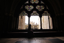 Silhouette of a woman sitting near a stained glass window in an ancient cathedral.