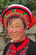 Smiling woman in a traditional hat from a minority tribe in China