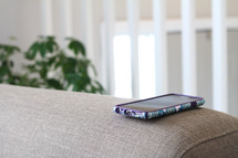 cellphone on a couch arm