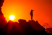 silhouette of a woman stretching on a mountain under a vibrant sky at sunset