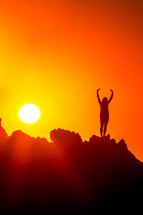 woman standing on a mountain at sunset with raised hands