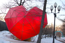 Heart-shaped umbrella in a snow-covered park.