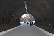 People walking through wooden tunnel .