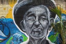 Graffiti painting of an elderly man on a brick wall background