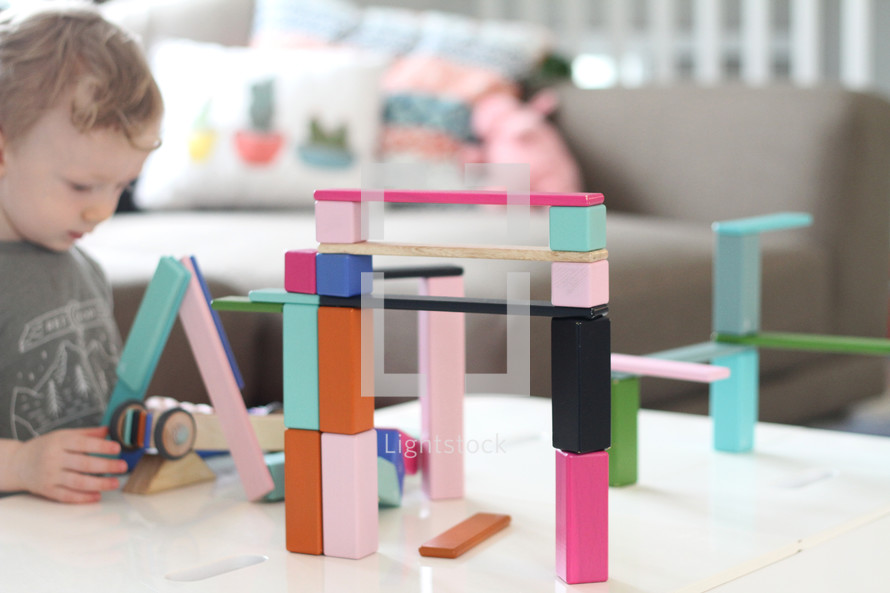 toddler boy playing with building blocks