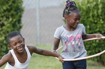 children playing outdoors with a hula hoop