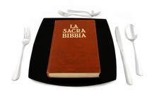 Metaphoric concept with bible in the plate with cutlery on white table.