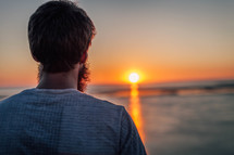 guy stares at the sunset on the ocean