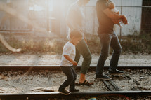 a young family walking on railroad tracks outdoors