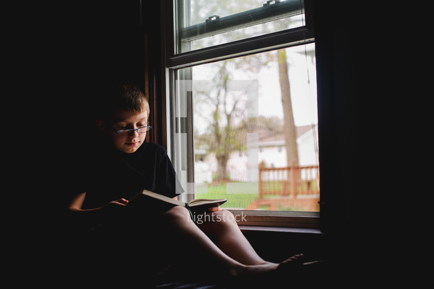 a boy reading a book in front of a window