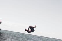 boy doing a flip into a lake
