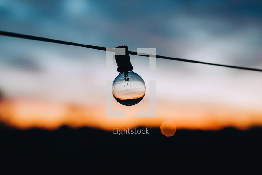 hanging lightbulb at sunset