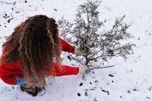 a woman cutting down a tree in the snow