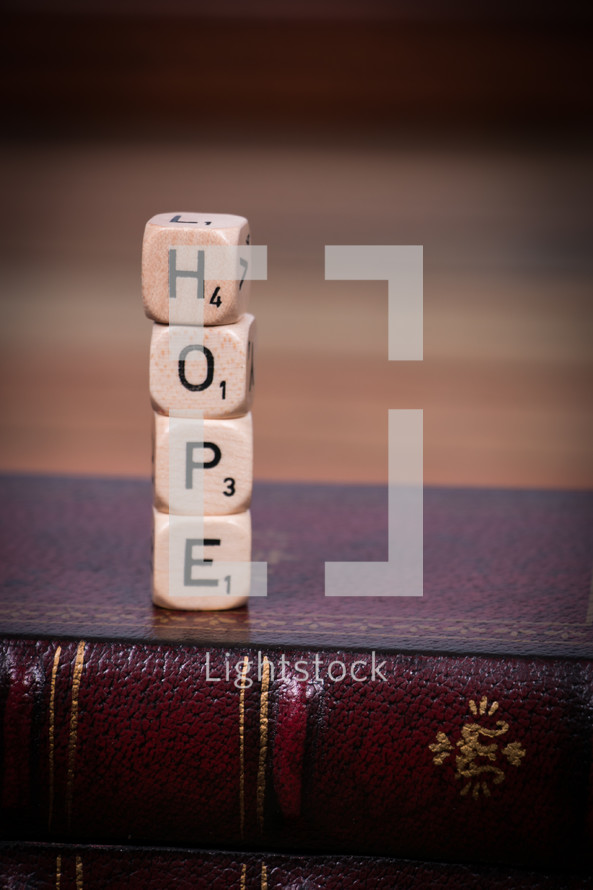 "Stacked dice, spelling ""hope,"" on a leather Bible."