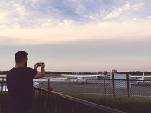 a man taking a picture of planes at an airport runway