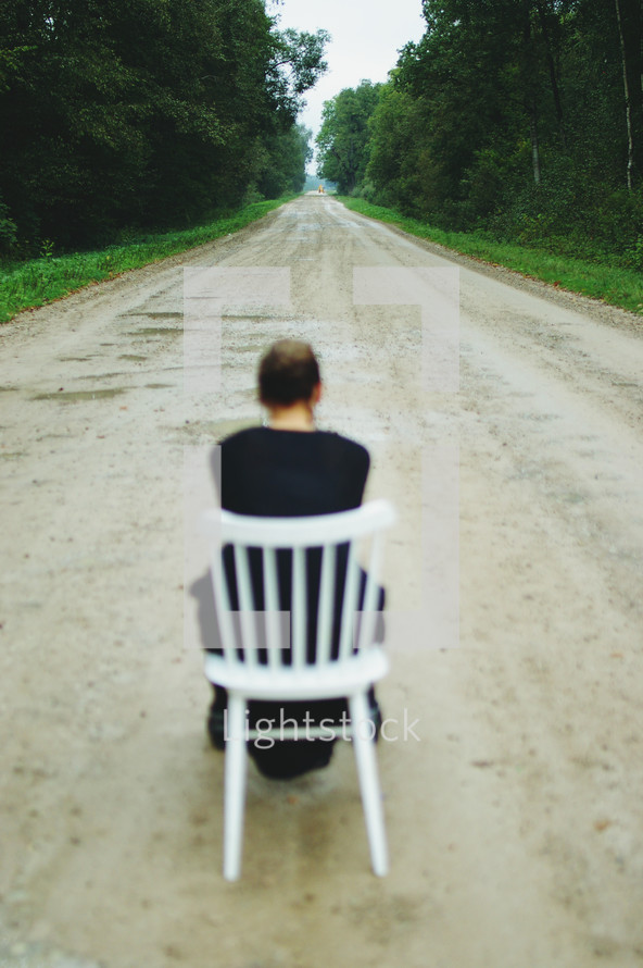 a woman sitting in a chair in the middle of a dirt road