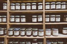 mason jars of preserves on a cupboard shelf