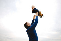 a father holding his infant son in the air
