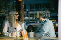 Window view of a couple having coffee.