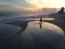 a little girl walking on a beach at sunset