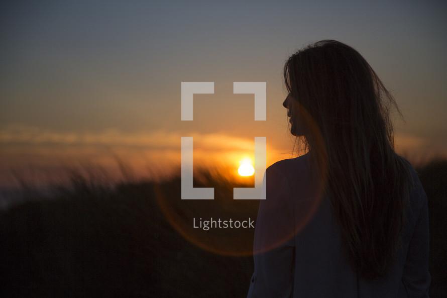 a woman watching a sunset