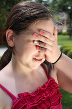 teen girl covering her eyes with her hand