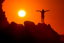 silhouette of a woman standing on a mountain with outstretched arms at sunset