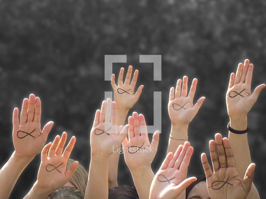 hands raised with Jesus fish
