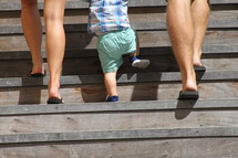 a mother and father walking up a flight of stairs with their toddler son