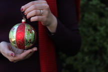 a woman holding a Christmas ornament