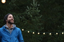 a bearded man standing in a Christmas tree lot