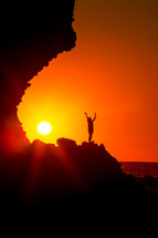 silhouette of a woman standing on a mountain with raised hands at sunset