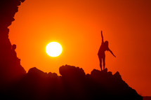 woman stretching on a mountain at sunset