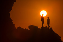 women standing at the edge of a cliff at sunset under a vibrant sky