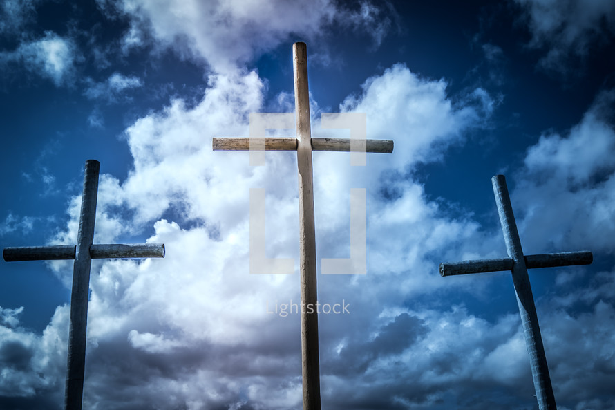 three crosses in front of clouds in a blue sky