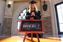 young woman in cap and gown praying on her knees in front of a sign that says where
