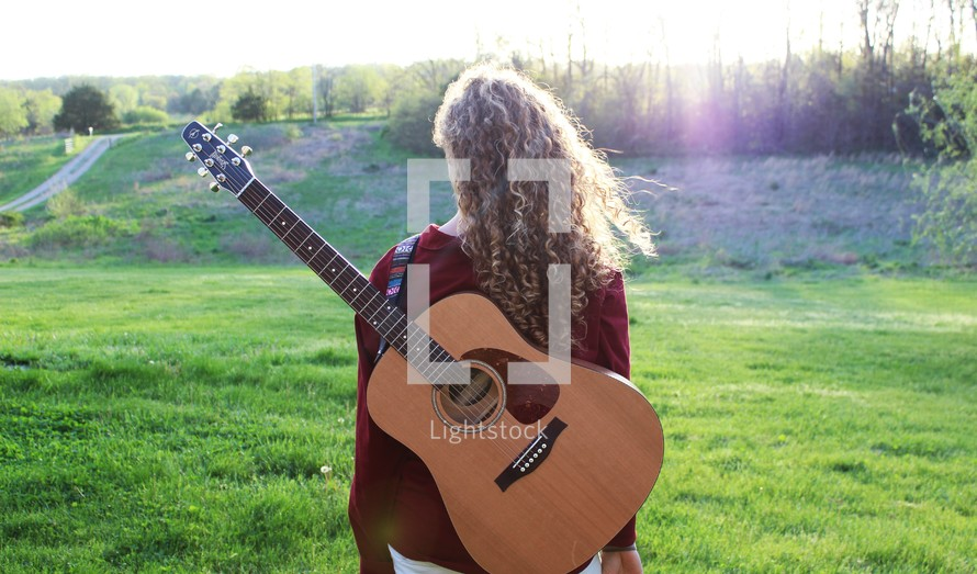 a woman standing outdoors with a guitar on her back
