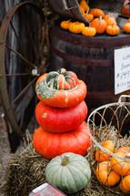 stacked pumpkins and wagon wheel
