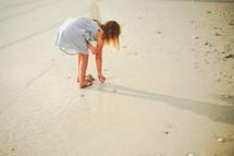 a girl in a sundress walking on a beach