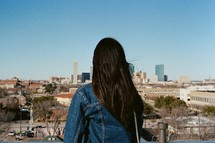a woman with her back to the camera looking out at a city