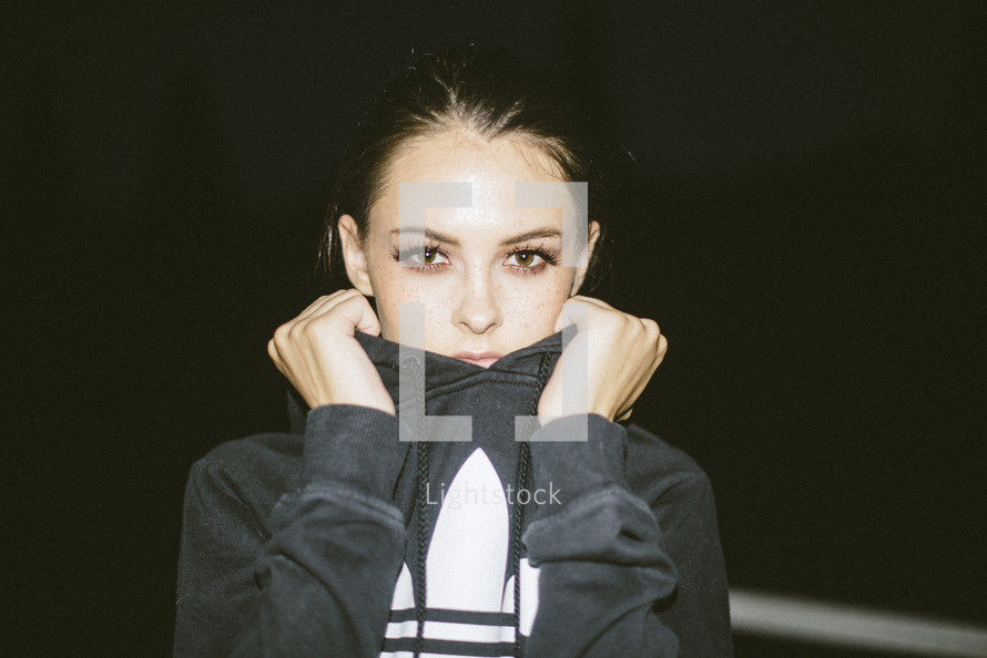 a teen girl pulling a hoodie over her face