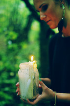 a woman carrying a candle in a mason jar outdoors