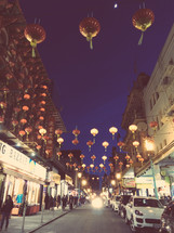 hanging paper lanterns over a street at night