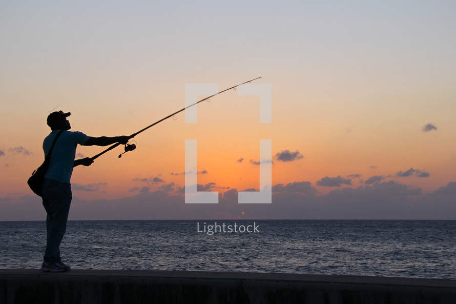 Man fishing on a beach at sunset