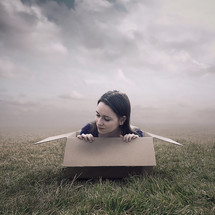 woman climbing out of a box