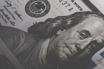 closeup of Benjamin Franklin on a one hundred dollar bill.